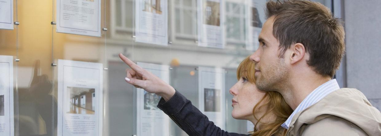 Man en vrouw staan in etalage te kijken bij de makelaar