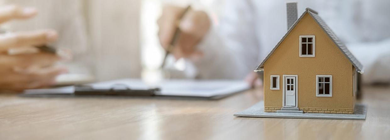 Een huis met op de achtergrond een adviseur in gesprek over de hypotheek
