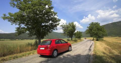 twee rode autos rijden door het natuur met bergen