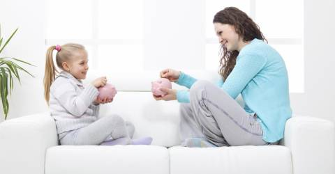 Moeder en dochter met spaarvarken op de bank