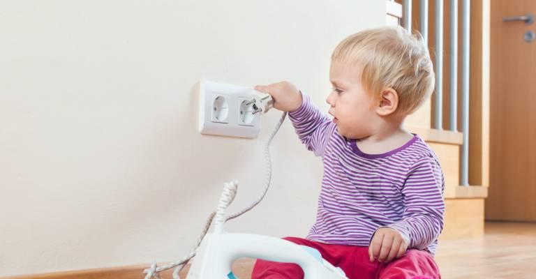 Kind zit te spelen met het stopcontact